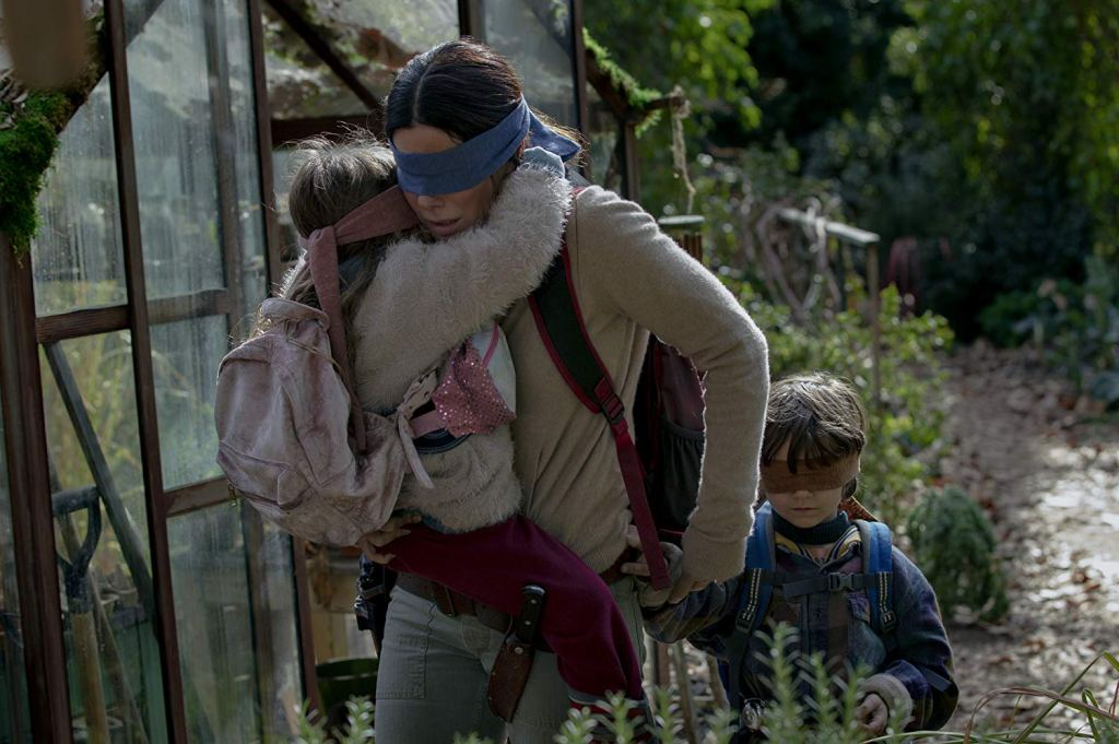 Movie still from 'Bird Box' showing Sandra Bullock with a boy and a girl, all wearing blindfolds.