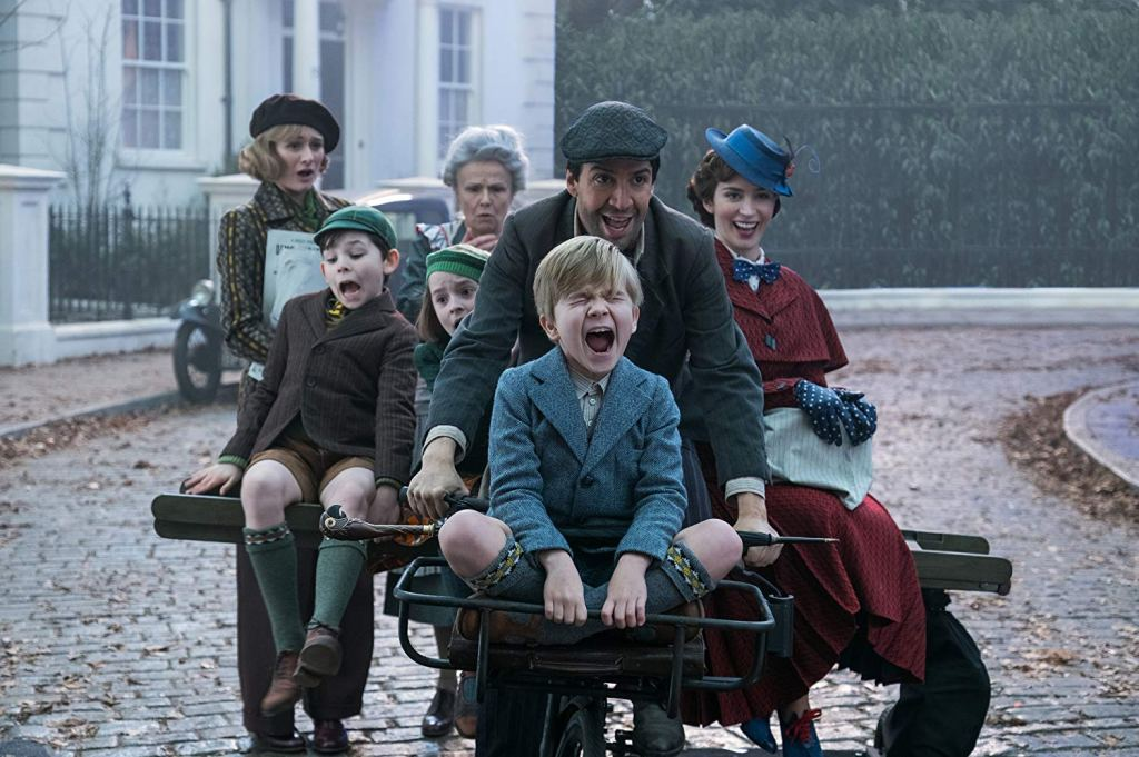 Movie still showing Mary Poppins and Co. riding a bicycle.