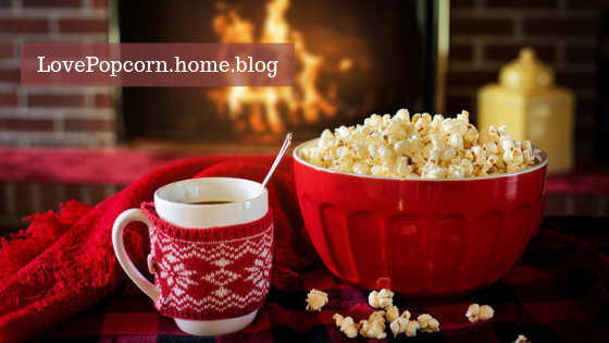 Cup of hot chocolate and bowl of popcorn in front of a fire.