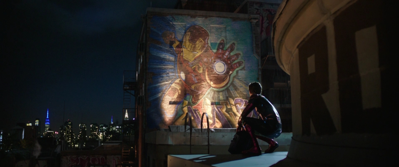 Movie still from Spider-Man: Far From Home showing Peter Parker looking at a mural of Iron Man.